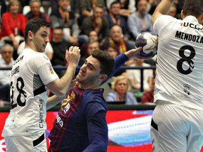 El jugador del Barcelona Fábregas (c) lanza ante David Mendoza (d) y Sergio López, del Cuenca.