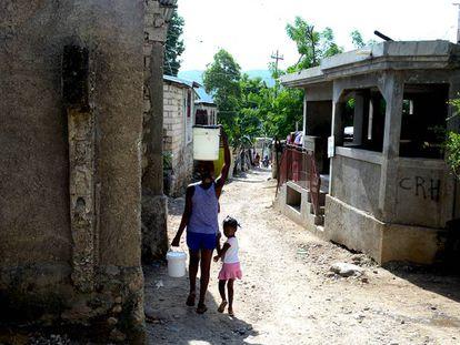 Una mujer carga con agua tras comprarla en un kiosko de Jacmel (Haití).