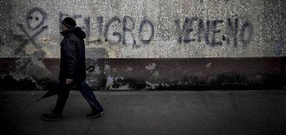Un vecino pasa ante una pintada contra el lindano en las viviendas sociales de Torneiros (O Porriño).