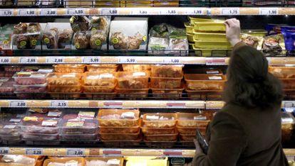 Una mujer elige productos cárnicos en un supermercado.