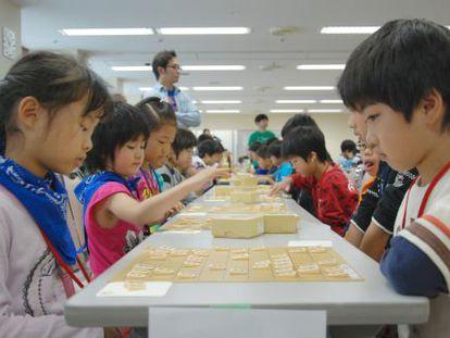 Dos niños juegan en un torneo de shogi.