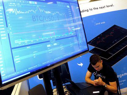 Un hombre junto a una pantalla con la cotización del bitcoin en 2018 en una conferencia en Nueva York sobre blockchain.