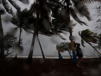 Una persona camina entre la lluvia y los fuertes vientos al paso de la tormenta Laura en Puerto Rico el domingo.