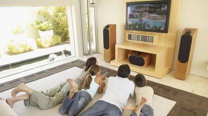 Una familia ve una película en el salón de casa.