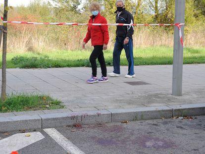 Una pareja pasa por el lugar del apuñalamiento de una mujer en Vitoria.