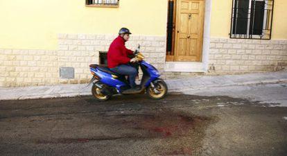 Un hombre pasa con su ciclomotor junto a los restos de sangre de la mujer degollada anoche en Benaguasil.