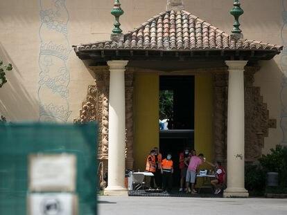 Un trabajador de la Cruz Roja toma la temperatura a una persona en la puerta de un pabellón para sin techo de Barcelona.