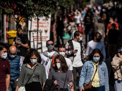 Decenas de personas caminan por la calle de la Montera en Madrid el primer día del confinamiento perimetral tras aprobar el estado de alarma.