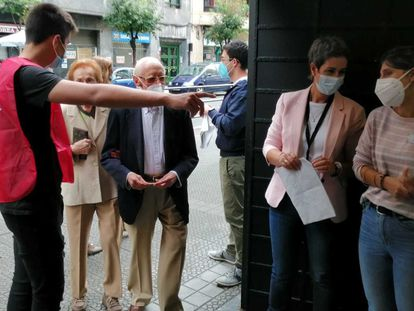 Unos votantes se dirigen a las urnas en un colegio electoral de Bilbao (Bizkaia) este domingo.