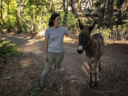 Cristina, junto a su burro, en la casa en la que vive cerca de Cenicientos (Madrid).