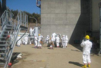 Fotografía facilitada por la empresa operadora de la central nuclear de Fukushima Daiichi, TEPCO, que muestra a sus trabajadores vestidos con monos especiales mientras trabajan en reestablecer el tendido eléctrico en los reactors 3 y 4 de la planta, en Okumamachi, en la prefectura de Fukushima (Japón).