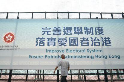 Un hombre pasa este martes ante un cartel en Hong Kong que promueve la reforma del sistema electoral.