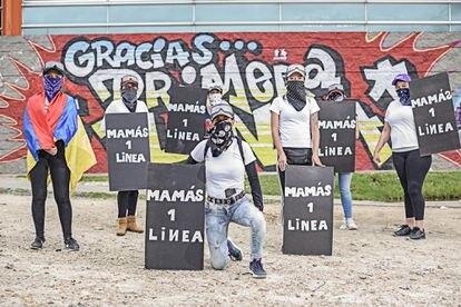 Algunas de las mamás de primera línea al frente de un mural en su honor.