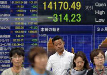 Un hombre se detiene delante de una pantalla con los resultados de la bolsa de Tokio (Japón). EFE/Archivo
