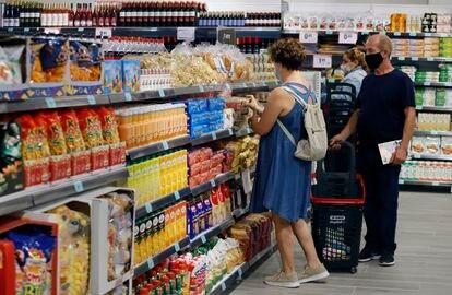 Unos clientes eligen productos en el supermercado.