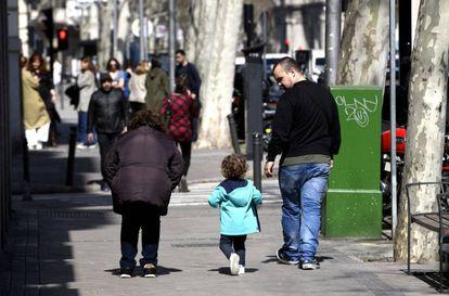 Unos padres pasan junto a su hija en el primer día sin colegio por el riesgo del coronavirus, en Madrid (España).