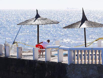 Un hombre realiza labores de mantenimiento en una terraza de playa en Dénia (Alicante).