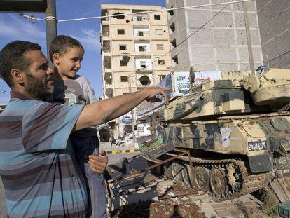 El brigadista Jalid Shabha, de 41 años, contemplaba ante el museo callejero de la revolución los tanques despanzurrados de Muamar el Gadafi, los trofeos de guerra que la gente de Misrata lograron arrebatar en 2011. Su hijo, Abdur, que nació el mismo 20 de octubre a las once de la noche en que la gente de Misrata capturaba y mataba a Muamar el Gadafi, sonríe entre los brazos de su padre, el 23 de febrero de 2016.