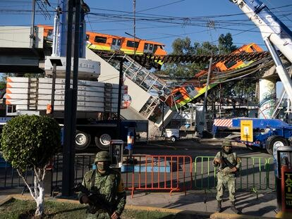 Una grúa maniobra para levantar el vagón caído al romperse una viga de la línea 12 del metro de Ciudad de México, este martes.