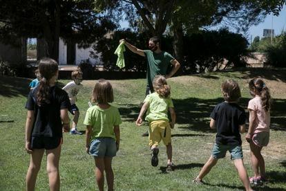 Niños jugando con su monitor en un campamento de verano en la provincia de Barcelona, el pasado lunes.