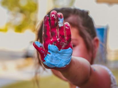 Una niña muestra su mano pintada.