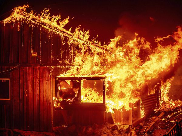 Flames shoot from a home as the Bear Fire burns through the Berry Creek area of Butte County, Calif., on Wednesday, Sept. 9, 2020. The blaze, part of the lightning-sparked North Complex, expanded at a critical rate of spread as winds buffeted the region. (AP Photo/Noah Berger)