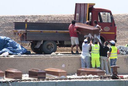 Varios voluntarios cargan los ataúdes con los cuerpos de algunos de los inmigrantes muertos, en el puerto de Lampedusa.