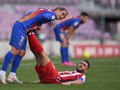 Koke, tumbado en el suelo, recibe la ayuda de Griezmann para estirar los gemelos durante los últrimos minutos del Barcelona-Atlético disputado el sábado en el Camp Nou. / David Ramos (GETTY IMAGES)