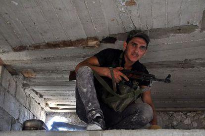 Un rebelde toma posiciones en un barrio de Alepo.