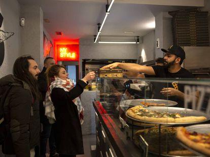 Guillermo y Alexandra recogen los packs con sobras de la pizzería Slais de Madrid compradas a través de la 'app' Too Good To Go.