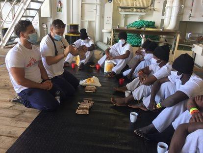 Philippe Juliany (izda) y Thomas Olufson explican a los migrantes a bordo del 'Geo Barents' cómo calentar el contenido de las bolsas de comida.