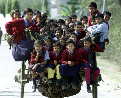 Más de 35 niños vuelven de la escuela subidos en un carro en las afueras de Nueva Delhi.