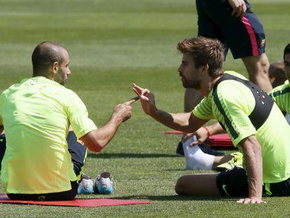 Piqué conversa con Mascherano en un entrenamiento del Barcelona.