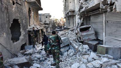 Soldados del Ejército sirio caminan en medio de una gran destrucción en el barrio de Bustan al-Basha, en Alepo, en el transcurso de su asalto para retomar la ciudad del control de los combatientes rebeldes.