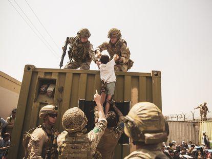 Militares ayudando a la evacuación de un niño este sábado en el aeropuerto internacional Hamid Karzai de Kabul.