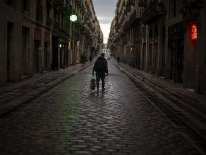 Un hombre camina por una calle del centro de Barcelona, ayer.