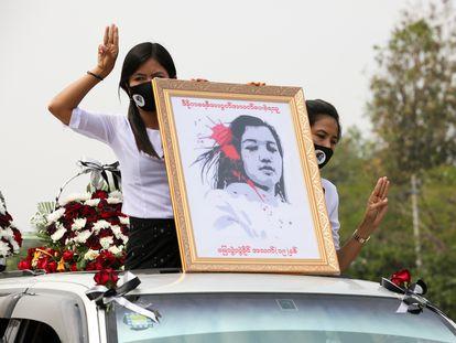 Varias mujeres sostienen un retrato de Mya Thwate Thwate Khaing, una manifestante muerta por disparos de la policía durante las protestas en Myanmar, en la comitiva del funeral por la joven el 21 de febrero.