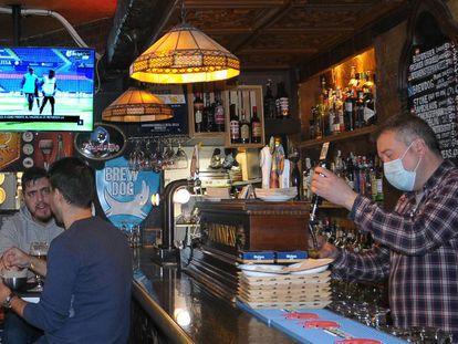 Víctor Rey sirve unas cervezas en su bar, El rincón del Greco. De fondo, un informativo de LaLiga Santander.