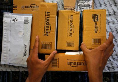 Un empleado de Amazon selecciona paquetes en una furgoneta en Ahmedabad (India), en marzo.