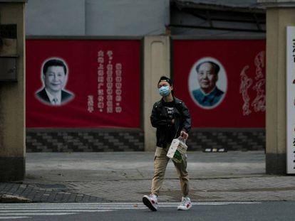 Un hombre con una máscara camina frente a los retratos del presidente chino Xi Jinping y el difunto presidente Mao Zedong, el pasado 10 de febrero en Shanghai.