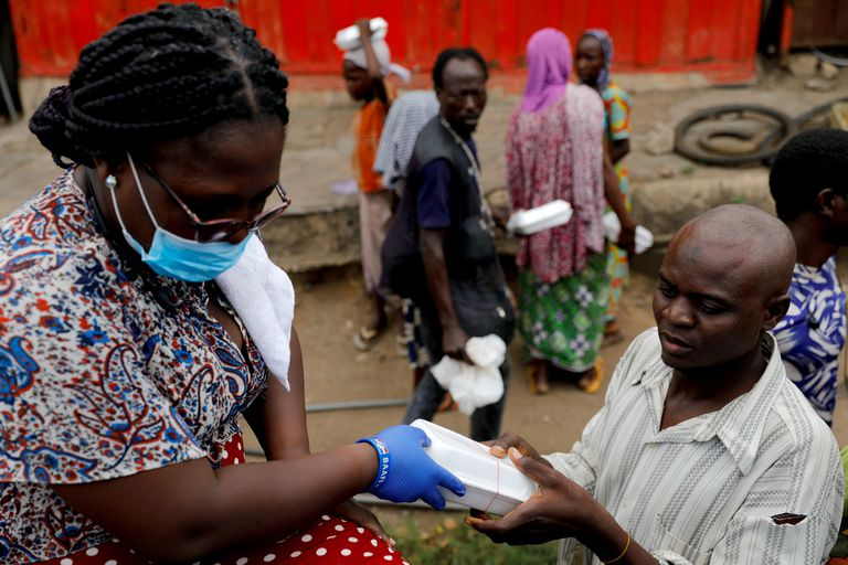 Una voluntaria distribuye comida a afectados por el confinamiento en Ghana.