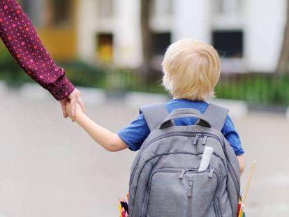 Un niño se dirige al colegio con su madre.