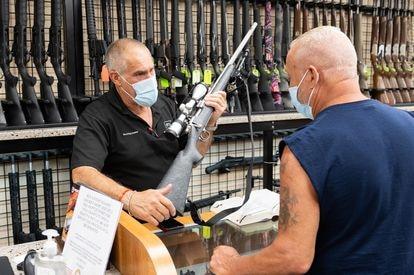 Un vendedor de armas muestra un rifle a un cliente en una tienda de Nueva York durante la pandemia.