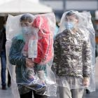 Passengers wearing masks and covered with plastic bags walk outside the Shanghai railway station in Shanghai, China, as the country is hit by an outbreak of a new coronavirus, February 9, 2020. REUTERS/Aly Song