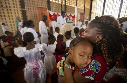Un niño duerme en brazos de su madre durante la misa en una iglesia de Garissa este domingo.
