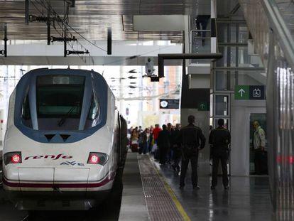 Viajeros en las escaleras mecánicas con sus maletas y un AVE en la estación de Atocha de Madrid.
