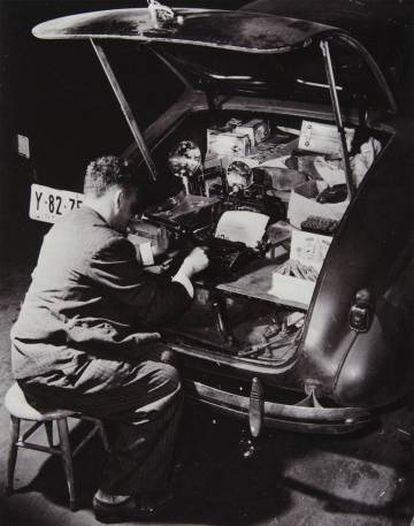 Weegee sentado en un taburete escribe a máquina en el maletero de su Chevrolet mientras fuma y se ilumina con una linterna, en 1942.