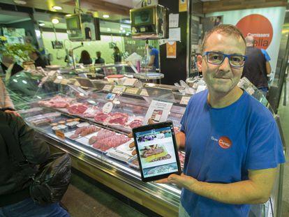 Un carnicero de Barcelona muestra su aplicación para la venta en internet, en 2017.