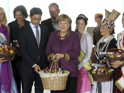 Angela Merkel y otros miembros de su Gobierno reciben manzanas en la Cancillería durante una celebración tradicional.