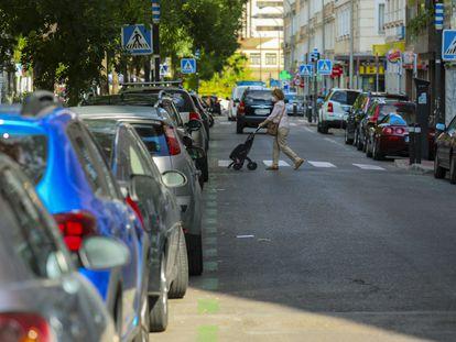 Una mujer cruza una calle en Madrid con vehículos aparcados en la zona de estacionamiento regulado.